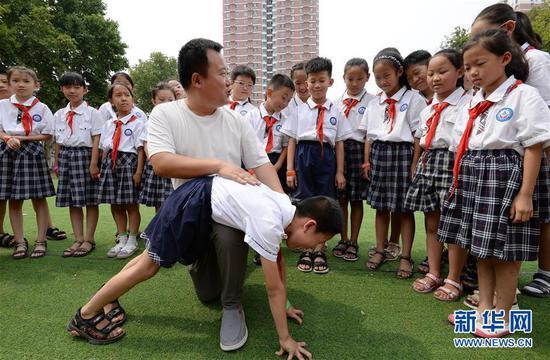7月4日,河北省邯郸市明珠实验小学的老师为学生们讲解防溺水急救技能。 暑期来临,各地学校纷纷组织学生开展暑期安全教育主题活动,让孩子们度过一个安全快乐的假期。 新华社发(郝群英 摄)