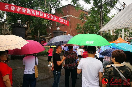 天津市第五十四中学考点外,不少家长撑伞站在门口等候、张望。崔新耀/摄