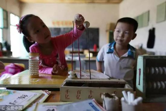 湖北某教学点,孩子们在教室里玩简陋的教学器具 / 视觉中国