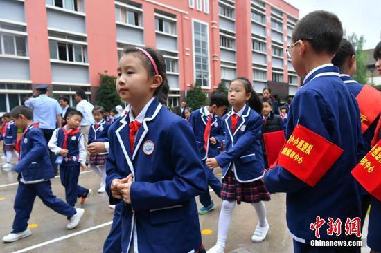 """巡逻队""""小队员戴着红袖套进行巡逻工作。"""