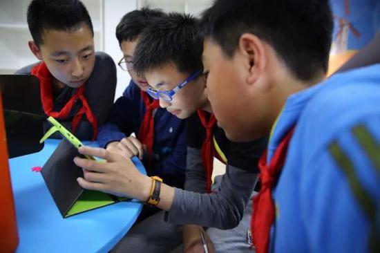 几位小学生正在用平板电脑设计作品。图片来源:半月谈