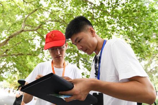 中国科学技术大学东校区,志愿者在解答新生(右)的问题。新华社供图