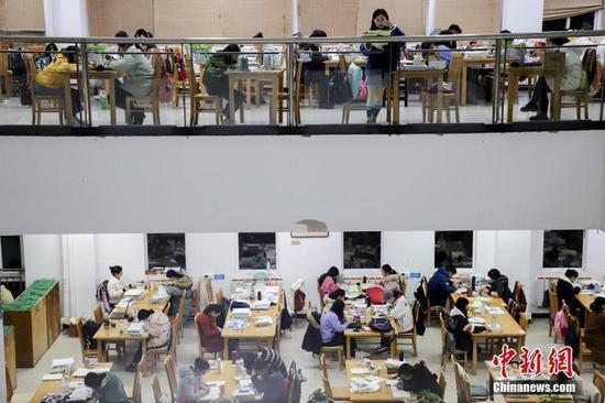 11月25日,贵州民族大学逸夫图书馆内,考研学生正在看书复习,为2020年全国硕士研究生招生考试做准备。 中新社记者 瞿宏伦 摄