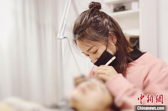 美睫师正在给顾客种植睫毛。受访者供图