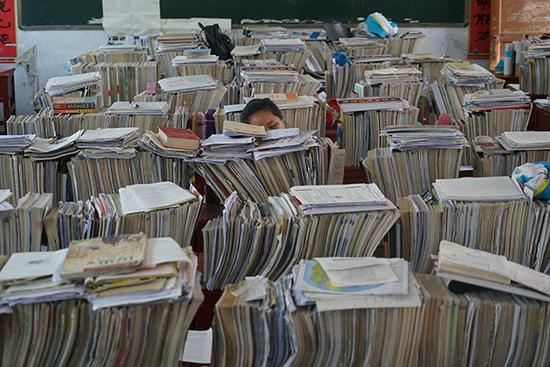 河南驻马店,高三年级的教室,桌子上高高堆积的书本几乎挡住了学生的头顶。视觉中国 图