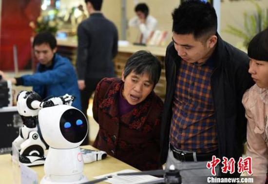 资料图:图为育儿机器人吸引市民眼球?!≈芤?摄