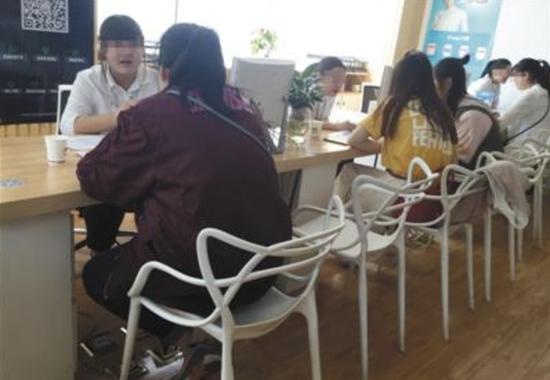 """4月25日,尚德机构国贸部,数名想通过自考获得学位的女士,正在咨询教育机构的""""老师""""们。A12-A13版摄影/新京报记者 大路"""
