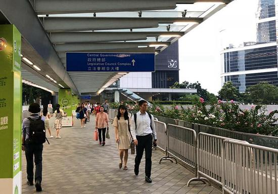 通往香港特区政府总部天桥上的工作人员行色匆匆。吴玉洁 摄