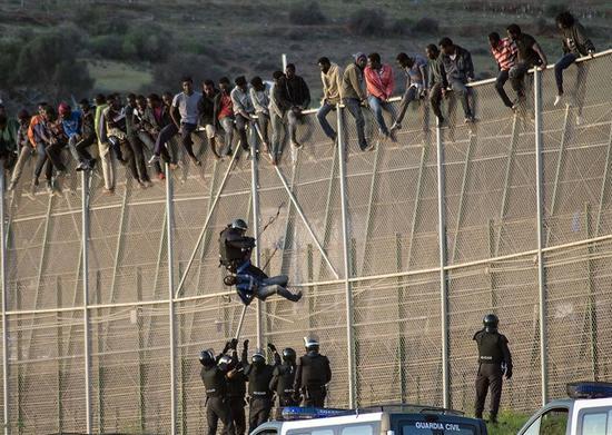"""2014年,西班牙非洲""""飞地""""梅利利亚移民硬闯入境事件,单日人数达2000人 图自世界报"""