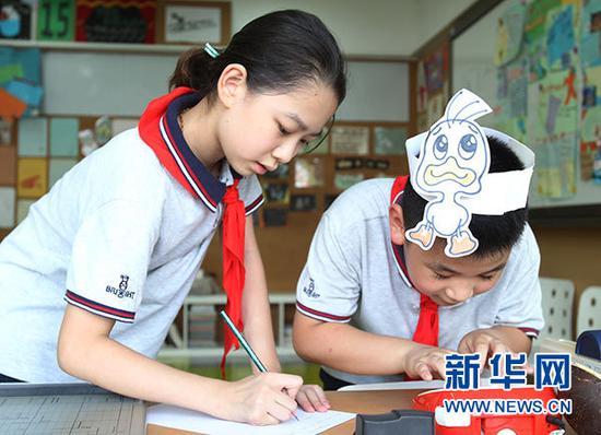 """9月3日,上海市天山第一小学的学生放学后在""""创意实验室""""编写英文情景剧剧本。"""
