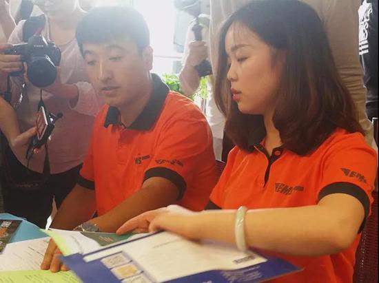 北京邮政速递工作人员把录取通知书及资助手册等材料一起封装进EMS信封中。