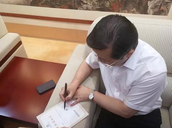 北语校长在刚出炉的首封录取通知书上签名。