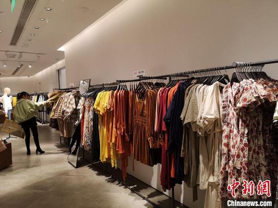 一位女性正在挑选衣服。 唐小晴 摄
