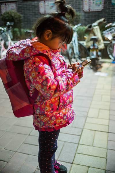 1月19日,在济南实验初中校门外,一位和姑姑来等表姐放学的小女孩,背着幼儿园的小书包,站在那里低头聚精会神地玩着姑姑的手机。