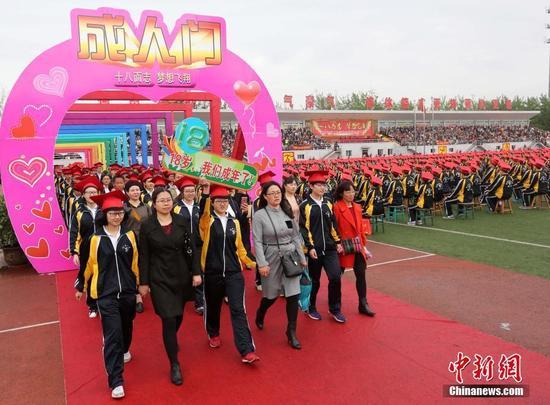 学生们戴上成人帽,走上红地毯,穿过成人门。