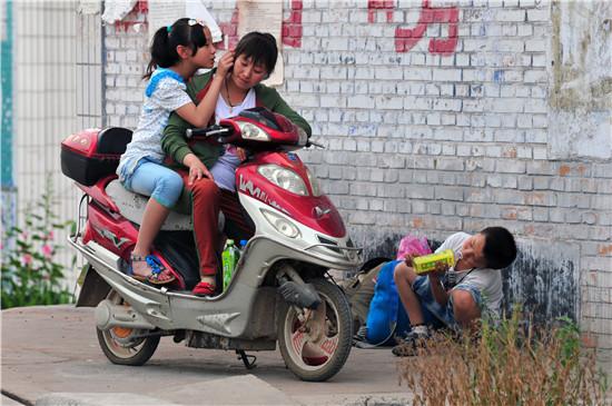 山西省永济市,母子三人正在路边等寄宿学校的校车,到20公里外的县城去上小学。姐姐上六年级,弟弟上二年级,两周回一次家。视觉中国供图(资料图片)