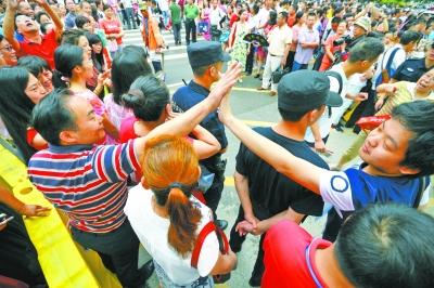 昨天,市第一中学考点,送考生的老师们站在考场外与进场的考生击掌助威。记者金振强 摄