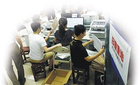 工作人员将高考答卷进行扫描
