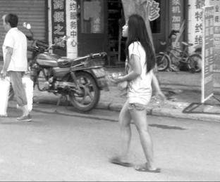 第三次被救助送回家前的小兰在街上流浪。