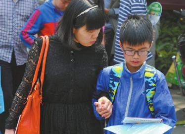 娃娃一出校门家长迎上去了解测试情况。