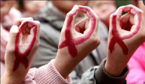 资料图:中国安徽省学生在对抗艾滋病的宣传活动中在手上涂出红丝带图。