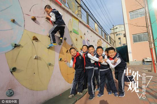 """2013年12月4日,北京,为培养男孩的阳刚之气,朝阳实验小学启动""""小男子汉""""培养计划,为男孩专门开设课程,给男孩""""加钢""""。图为朝阳实验小学的学生在老师的指导下,进行攀岩比赛。(视觉中国)"""