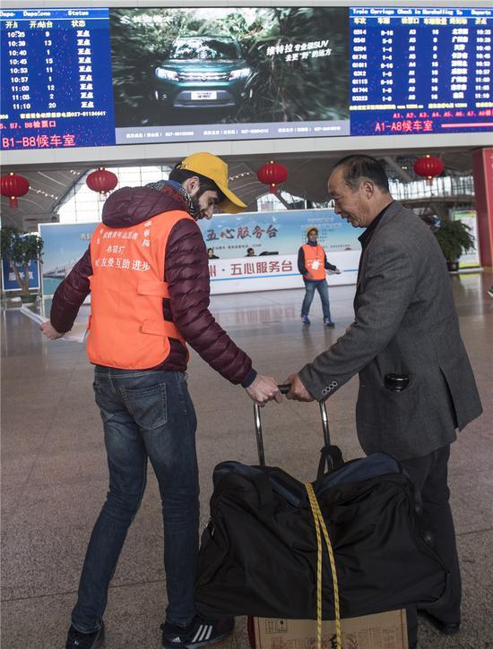 外国志愿者帮助老年旅客拖行李。新华社记者吴植摄