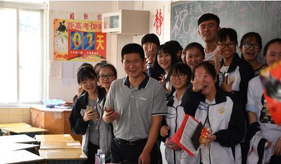 学生与老师合影留念,告别自己的高中生涯。