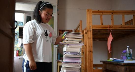 """高三学生崔媛媛与她的书籍告别,她戏称这些书籍为""""毛坦厂特产""""。"""