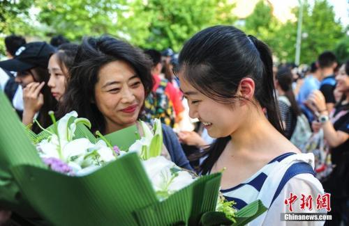 資料圖:山東濟南眾多考生手捧鮮花在家長的簇擁下歡快告別高考。中新社記者 張勇 攝