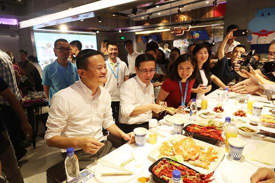 7月14日,阿里巴巴董事局主席马云和CEO张勇等人在盒马鲜生品尝刚刚出炉的海鲜。