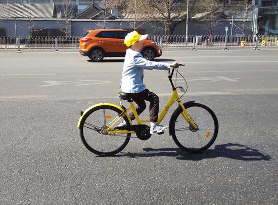 北京西单路口附近,一位正在骑行共享单车的儿童。杜佳/视觉中国供图