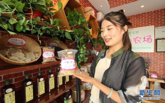 胡盼盼正在向客人展示农家锅巴的新包装。