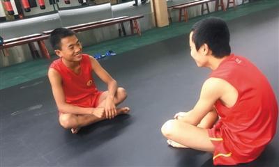 阿坝州马尔康训练馆,小伍(左)和小伙伴聊天。新京报记者 陶若谷 摄