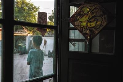 8月8日,山东郓城县西张楼村,张超12岁的弟弟独自一人站在屋外望着大门口。他的父亲前往天津询问案情进展未回,母亲因极度悲伤卧床不起,屋里屋外全靠弟弟张罗。新京报记者 彭子洋 摄