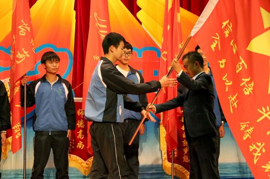 云南衡水中学滇池校区年级主任石刚为各班级授班旗