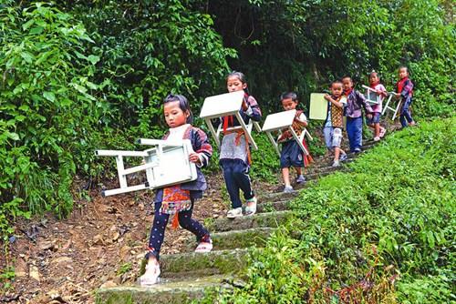9月5日,久甲小学的学生在搬运爱心单位送来的新课桌凳。