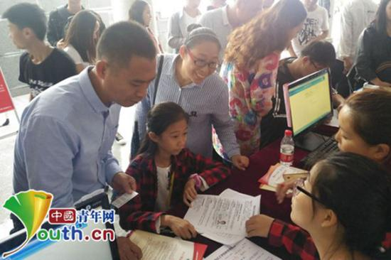 张易文在父母的陪护下办理入学手续。