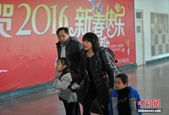 2月3日,山西太原火车站,一对夫妻领着他们的两个孩子匆忙赶车。中新社记者 韦亮 摄