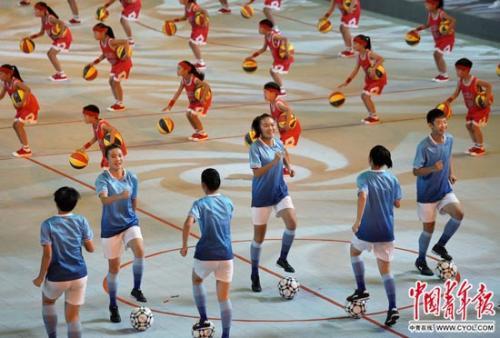 9月3日,第十三届全国学生运动会开幕式,文艺演出上的球技秀《薪火相传》,学生们在同一场地进行足球操和篮球操的表演。 陈剑/摄