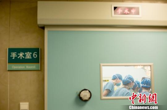 """""""手术中""""的红灯亮起,医生开始""""战斗""""。 范丽芳 摄"""