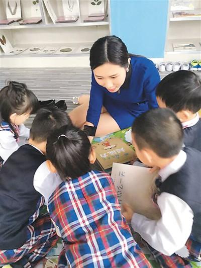 图为陈露曼在幼儿园里同孩子一起玩耍