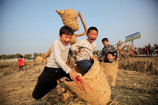 江苏泗洪,孩子们在稻米文化节的稻草人艺术展展区快乐地玩耍。视觉中国 资料