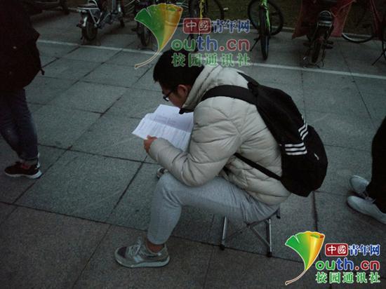 考研学生坐在小马扎上认真地学习。中国青年网通讯员 闫春旭 摄