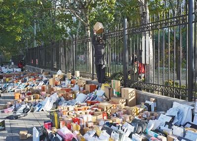 昨日,清华大学北二门,快递人员将包裹递给护栏内的学生。 新京报记者 王飞 摄