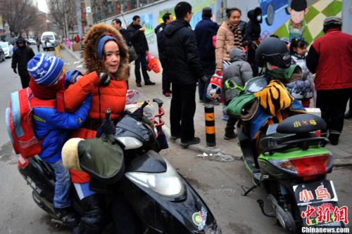 资料图:家长骑电动车把孩子送到学校。中新网记者 金硕 摄