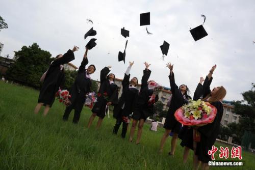 资料图:留学生抛帽子庆祝毕业。中新社发 赵琳露 摄