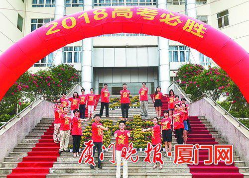 """厦门六中老师穿上大红T恤,在""""必胜""""花坛造型前为考生加油。"""