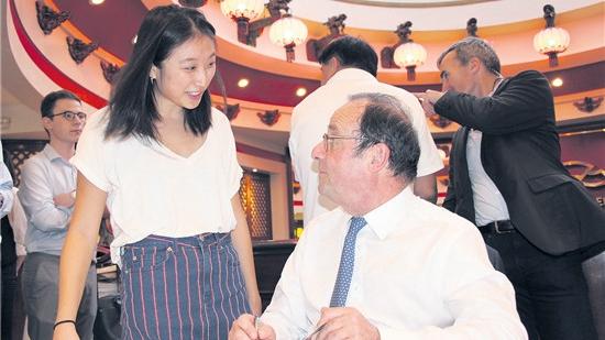 曾永革的女儿Claire在法国前总统奥朗德新书签售会上与其交谈。(图片来源:曾永革 摄)