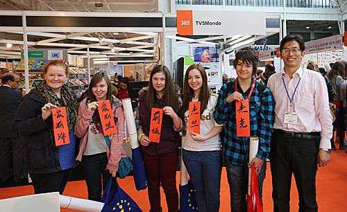 在英国伦敦举行的语言展上,观众在中国展台前展示写着自己中文名字的书法作品。(新华社)